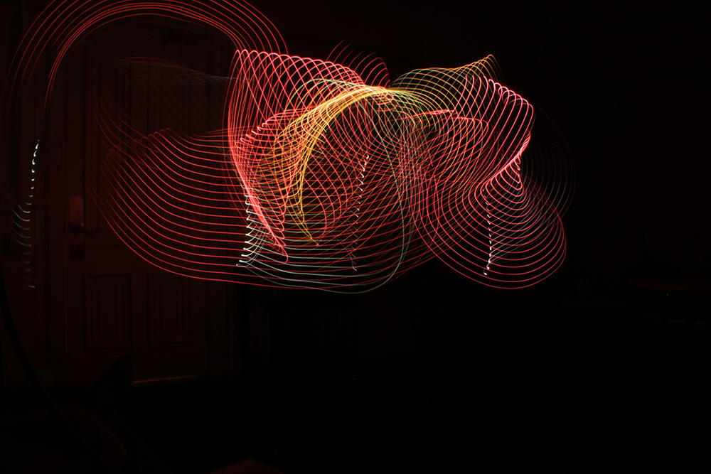 a long exposure photograph that shows bands of bright color spread across space in big, dramatic swirls